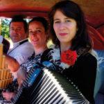 Le trio HerMaNa en photo dans une vieille voiture rouge