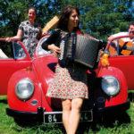Le trio HerMaNa en photo à la sortie d'une vieille voiture